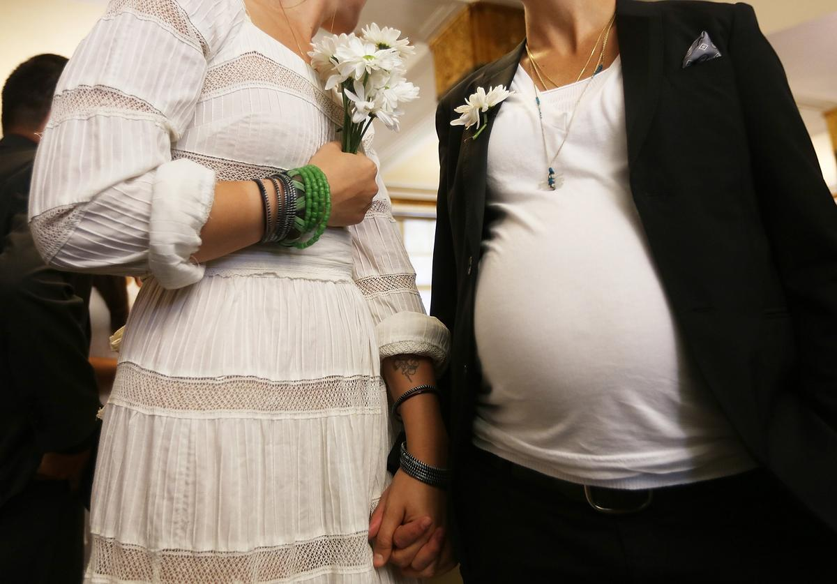 Stefanie Berks (L) and Daisy Boyd hold hands by Boyd's pregnant belly before their marriage ceremony at the Manhattan Marriage Bureau two days after the U.S. Supreme Court ruling on DOMA on June 28, 2013 in New York City. The high court struck down the Defense of Marriage Act (DOMA) and ruled that supporters of California's ban on gay marriage, Proposition 8, could not defend it before the Supreme Court. Boyd is 8 1/2 months pregnant and the pair said they planned to get married today before the ruling came down.