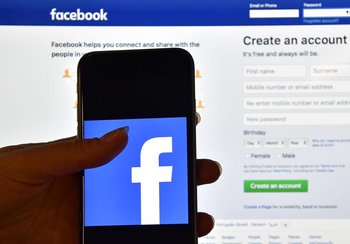 A person holds an iPhone displaying the Facebook app logo in front of a computer screen showing the facebook login page on August 3, 2016 in London, England.