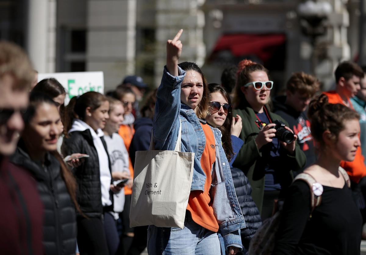 A demonstrator shows their disapproval as they pass the Trump International Hotel with several hundred high school students marching from the White House to the U.S.