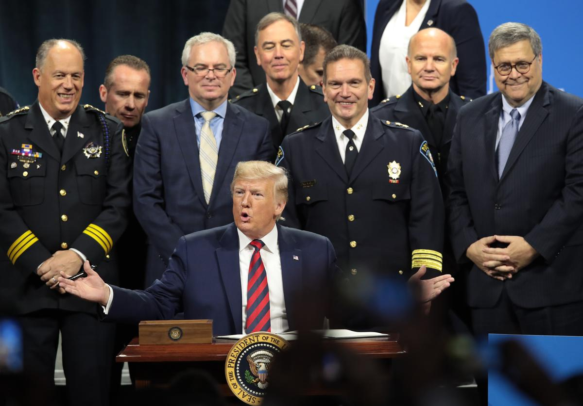 U.S. President Donald Trump signs an executive order to create a commission to study the administration of justice following an address to the International Association of Chiefs of Police (IACP) convention on October 28, 2019 in Chicago, Illinois. Trump is expected to attend a fundraiser hosted by Chicago Cubs co-owner and Trump Victory Committee Finance Chairman Todd Ricketts at Trump Tower following the address. The visit is Trump's first official visit to the city since protesters forced him to cancel a 2016 campaign rally in the city.