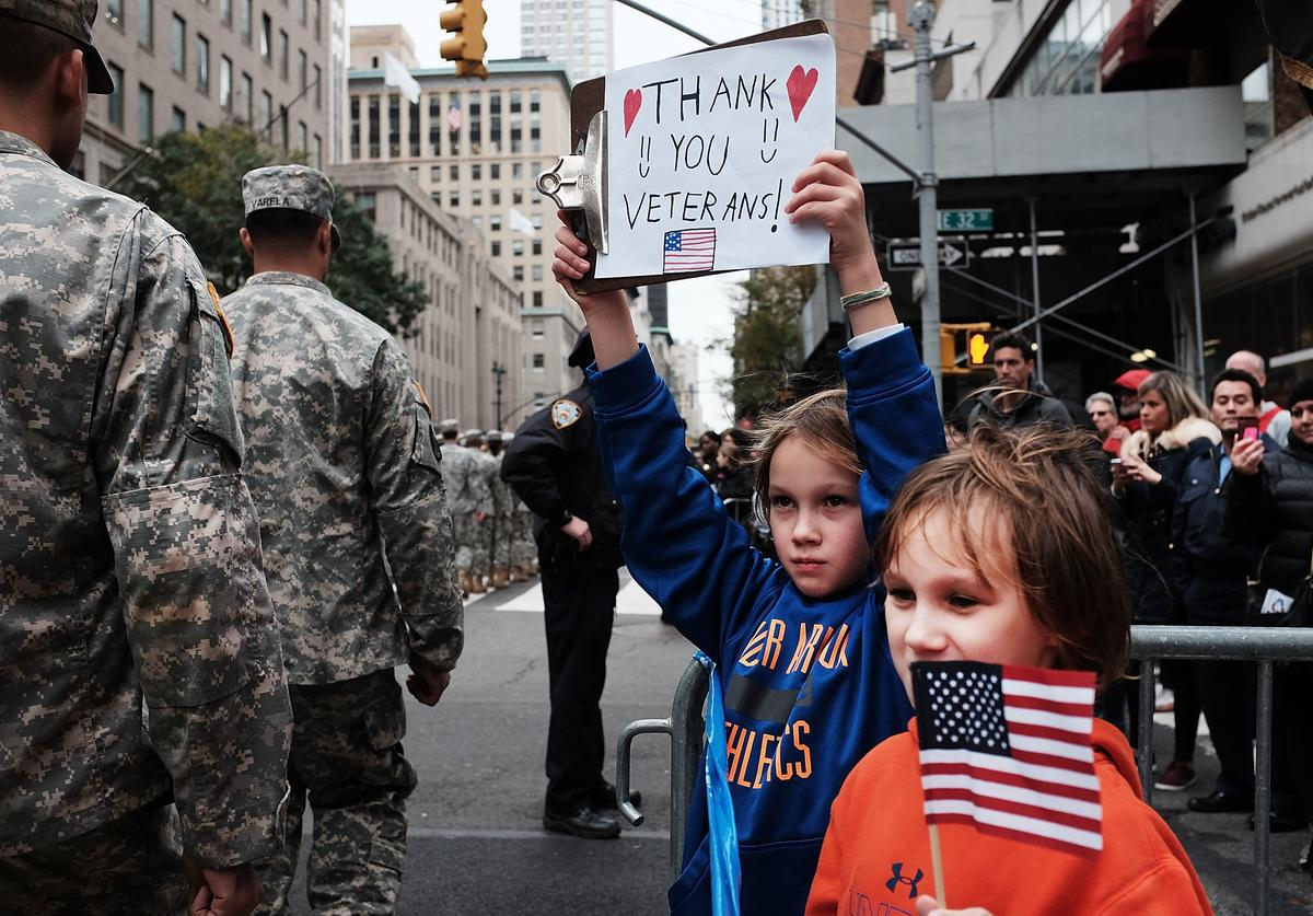 Gavin Kinney ,left, and his brother Rigel hold up a sign thanking veterans at the nation's largest Veterans Day Parade in New York City on November 11, 2015 in New York City