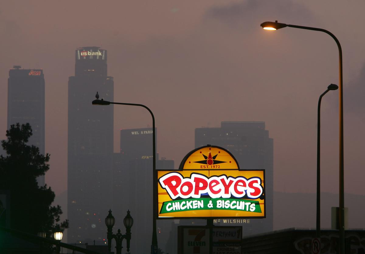 A Popeyes fast-food restaurant sign glows above the city skyline on July 24, 2008 located in the Figueroa Corridor area of South Los Angeles, Los Angeles, California