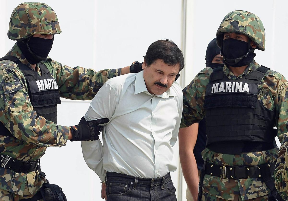 "Mexican drug trafficker Joaquin Guzman Loera aka ""el Chapo Guzman"" (C), is escorted by marines as he is presented to the press on February 22, 2014 in Mexico City. Mexican drug lord Joaquin ""El Chapo"" Guzman has escaped from a maximum-security prison for the second time in 14 years, sparking a massive manhunt Sunday and dealing an embarrassing blow to the government. AFP PHOTO/Alfredo Estrella"