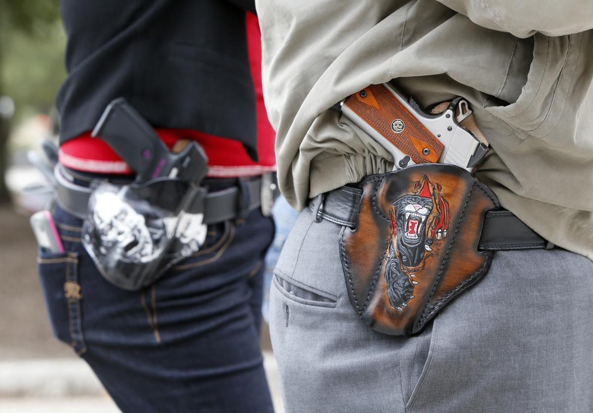 Art and Diana Ramirez of Austin with their pistols in custom-made holsters during and open carry rally at the Texas State Capitol on January 1, 2016 in Austin, Texas. On January 1, 2016, the open carry law takes effect in Texas, and 2nd Amendment activists hold an open carry rally