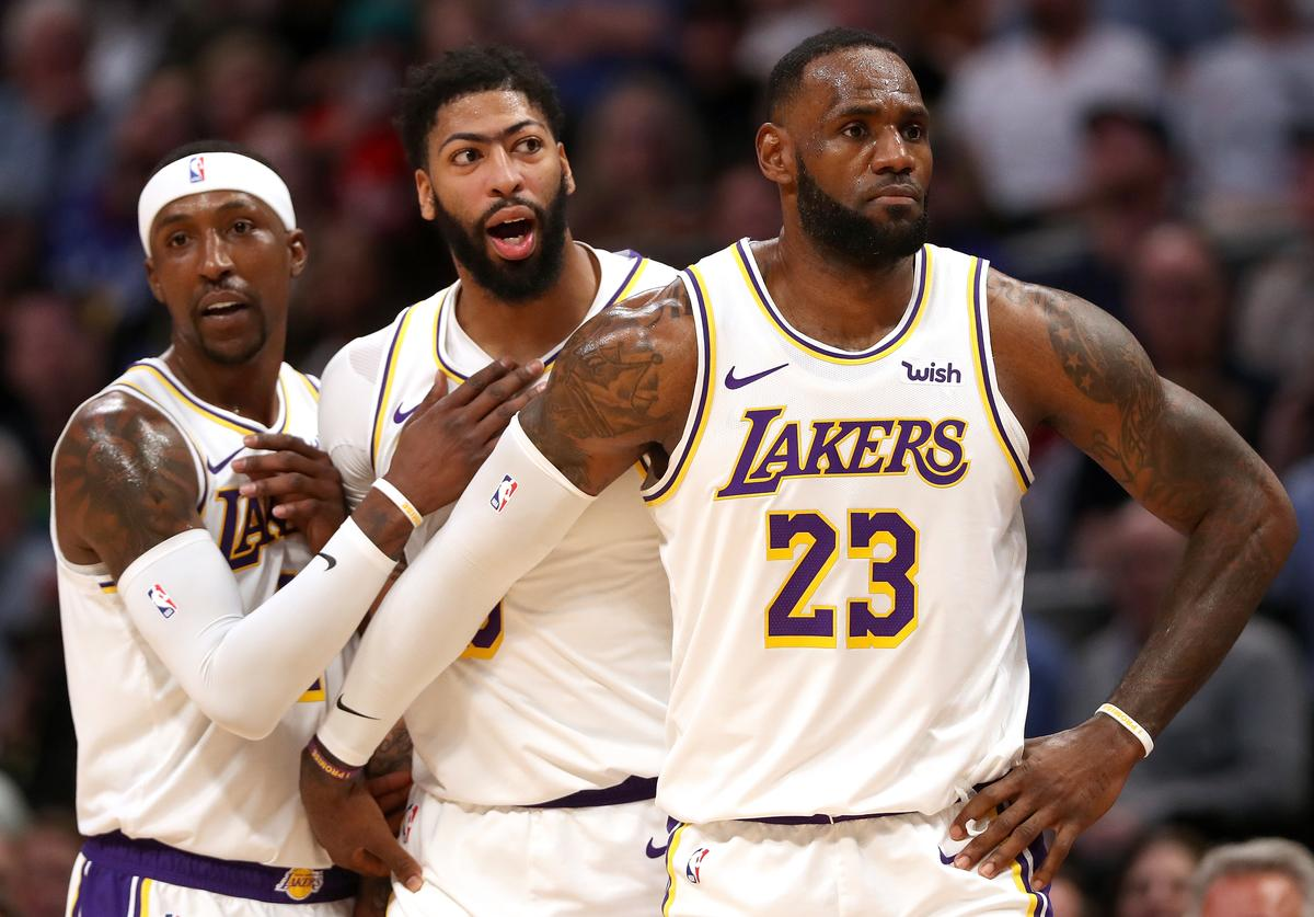 Anthony Davis #3 of the Los Angeles Lakers is restrained by Kentavious Caldwell-Pope #1 and Lebron James #23 after being called for a foul against the Denver Nuggets in the third quarter at Pepsi Center on December 03, 2019 in Denver, Colorado.