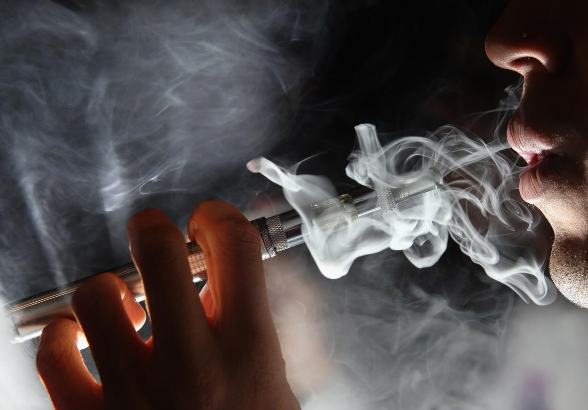 In this photo illustration, a man smokes an E-Cigarette at the V-Revolution E-Cigarette shop in Covent Garden on August 27, 2014 in London, England. The Department of Health have ruled out the outlawing of 'e-cigs' in enclosed spaces in England, despite calls by WHO, The World Health Organisation to do so. WHO have recommended a ban on indoor smoking of e-cigs as part of tougher regulation of products dangerous to children.