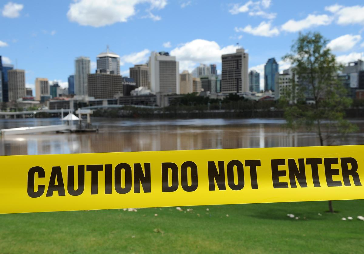 Council caution tape is seen to restrict access to the Brisbane river at South Bank as parts of southern Queensland experiences record flooding in the wake of Tropical Cyclone Oswald on January 29, 2013 in Brisbane, Australia. The river in the Brisbane CBD is expected to peak at 2.3 metres today - lower than the 2.6 metre peak predicted - but is still likely to flood low-lying properties and businesses. The flood crisis has claimed four lives so far, with the city of Bundaberg, Queensland faces the worst flooding in its history.