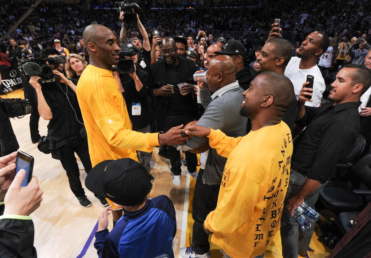 Kanye West greets Kobe Bryant at a basketball game between the Utah Jazz and the Los Angeles Lakers at Staples Center on April 13, 2016 in Los Angeles, California