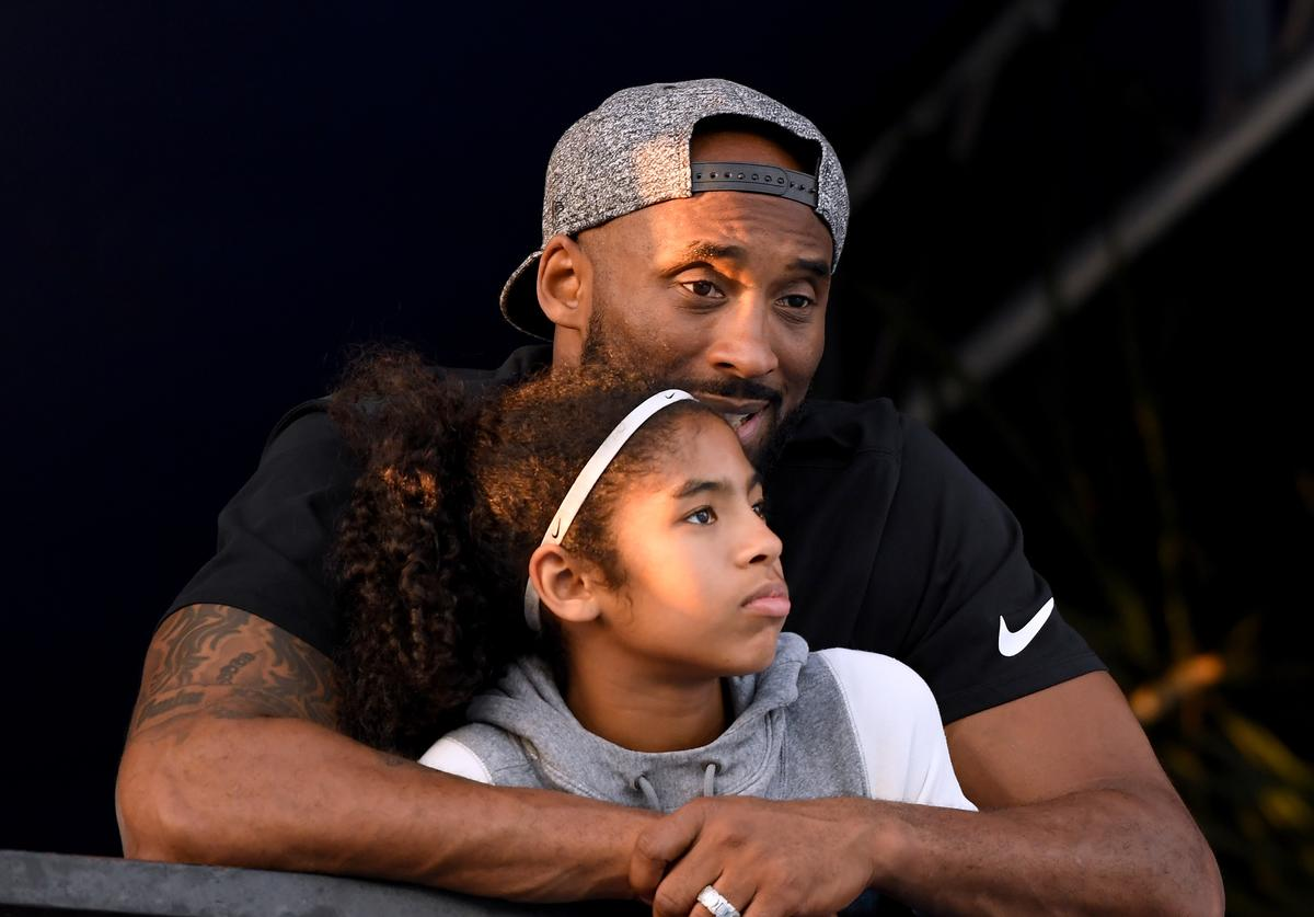 Kobe Bryant and daughter Gianna Bryant watch during day 2 of the Phillips 66 National Swimming Championships at the Woollett Aquatics Center on July 26, 2018 in Irvine, California