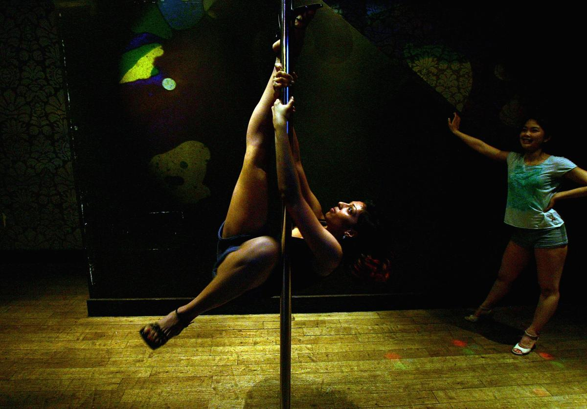 A woman performs pole tricks during a Polepeople pole dancing class May 3, 2006 in London, England. Since celebrities hailed pole dancing as the latest alternative to aerobics or yoga pole dancing has taken the United Kingdom by storm and has become the latest trend for females getting fit. The classes provide women with the opportunity to develop their upper-body strength and add sparkle to their sex life, while enjoying a female-only atmosphere which they find less regimented than traditional gym sessions.