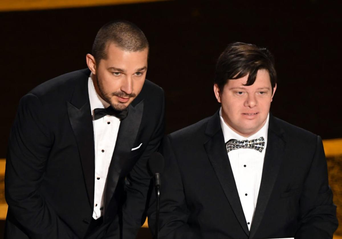 Shia LaBeouf and Zack Gottsagen speak onstage during the 92nd Annual Academy Awards at Dolby Theatre (Feb. 2020)
