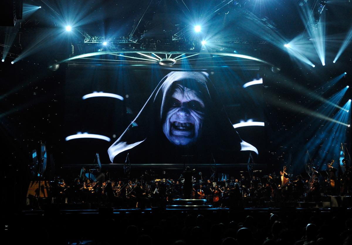 "ctor Ian McDiarmid's Emperor Palpatine character from the Star Wars series of films is shown on screen while musicians perform during ""Star Wars: In Concert"" at the Orleans Arena May 29, 2010 in Las Vegas, Nevada."