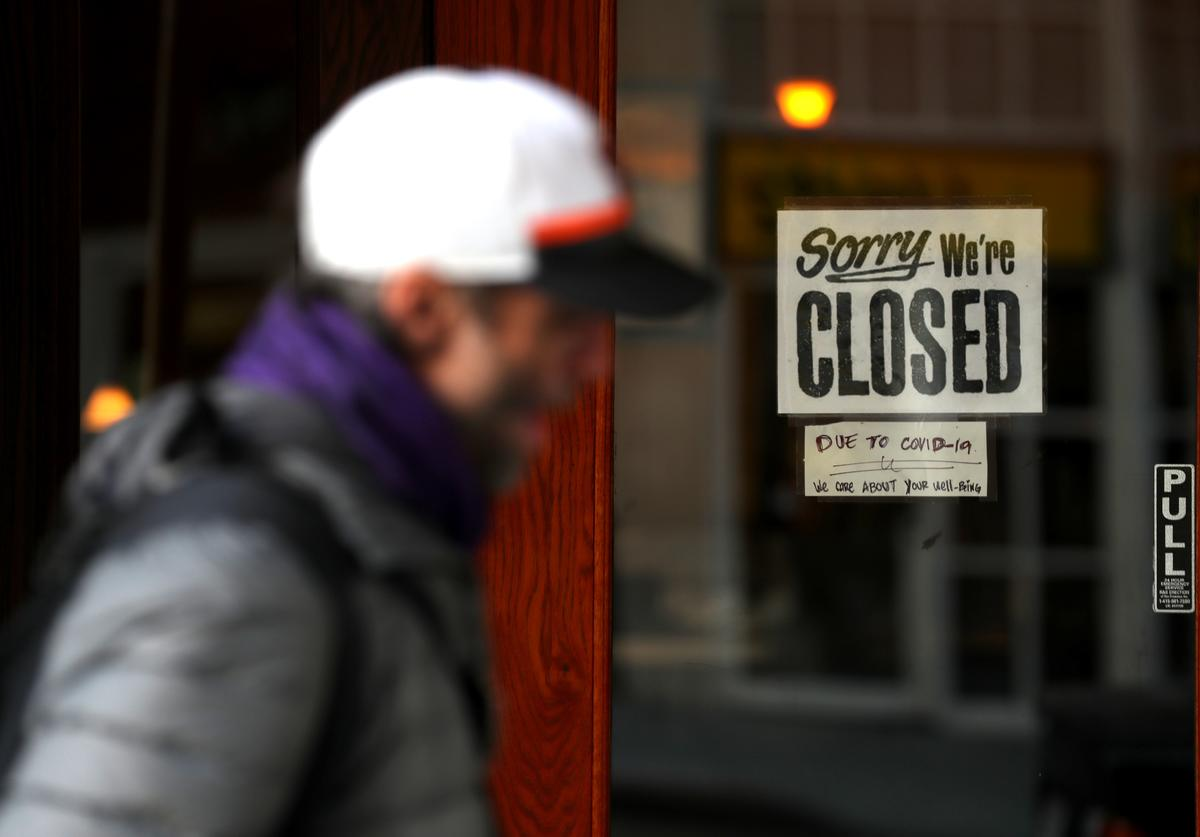 A pedestrian walks by a closed sign on the door of a restaurant on March 17, 2020 in San Francisco, California. Seven San Francisco Bay Area counties have ordered residents to shelter in place in an effort to reduce social interaction and slow the spread of COVID-19.