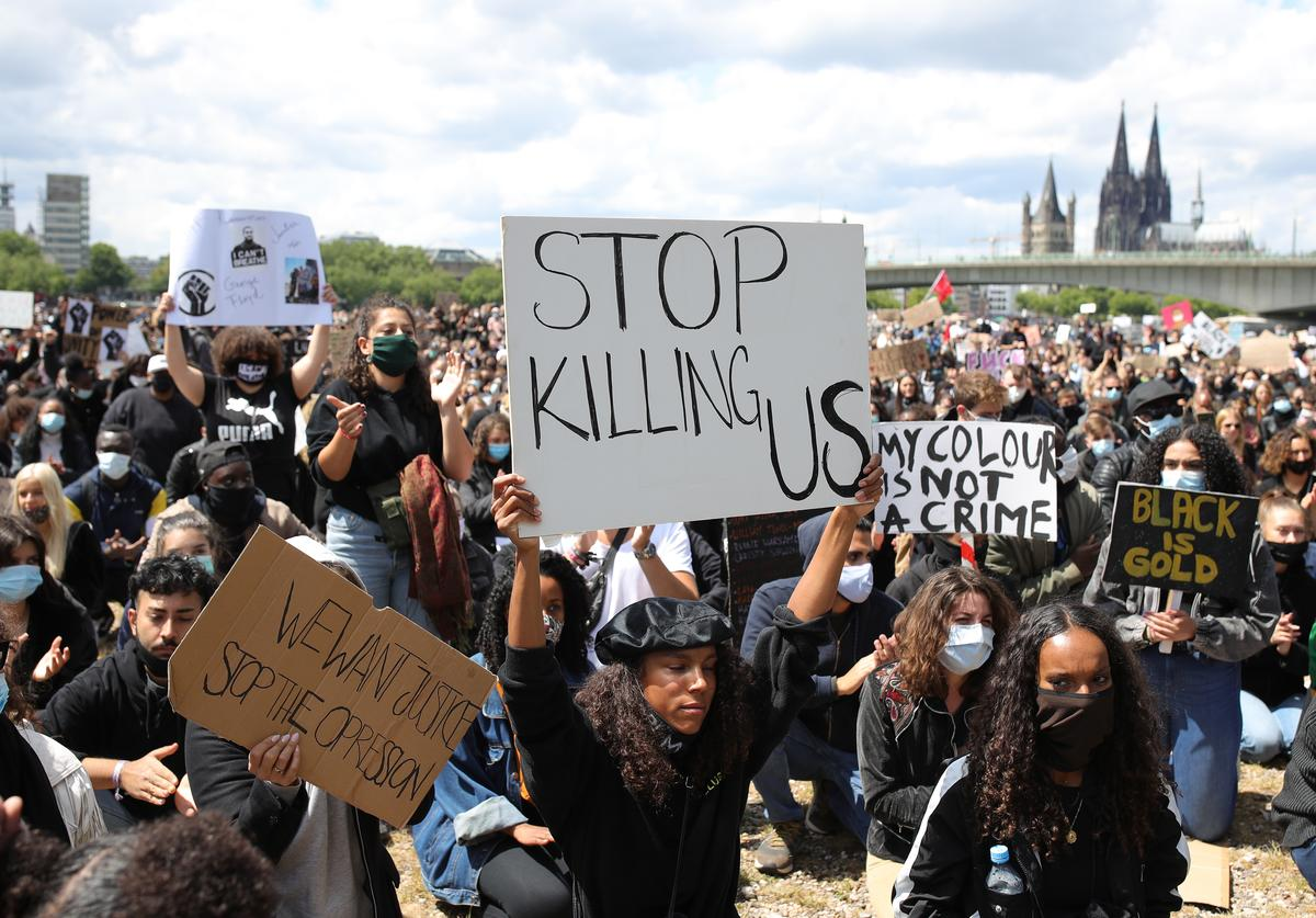People stand in silence for eight minutes and 46 seconds in tribute to George Floyd during a protest against racism and police brutality on June 06, 2020 in Cologne, Germany. Eight minutes and 46 seconds is the amount of time Minneapolis police officer Derek Chauvin held his knee on the neck of Floyd, an African-American, which resulted in Floyd's death. Similar demonstrations have been taking place across Europe, with over a dozen taking place across Germany today. Floyd's death, as well as the at times brutal recent response by police against protesters in the USA, have struck a chord with many people of color and others in Europe
