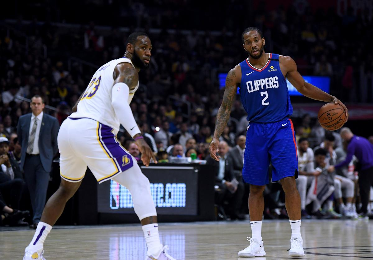 Kawhi Leonard #2 of the LA Clippers dribbles in front of LeBron James #23 of the Los Angeles Lakers during a 112-103 Lakers win at Staples Center on March 08, 2020 in Los Angeles, California.