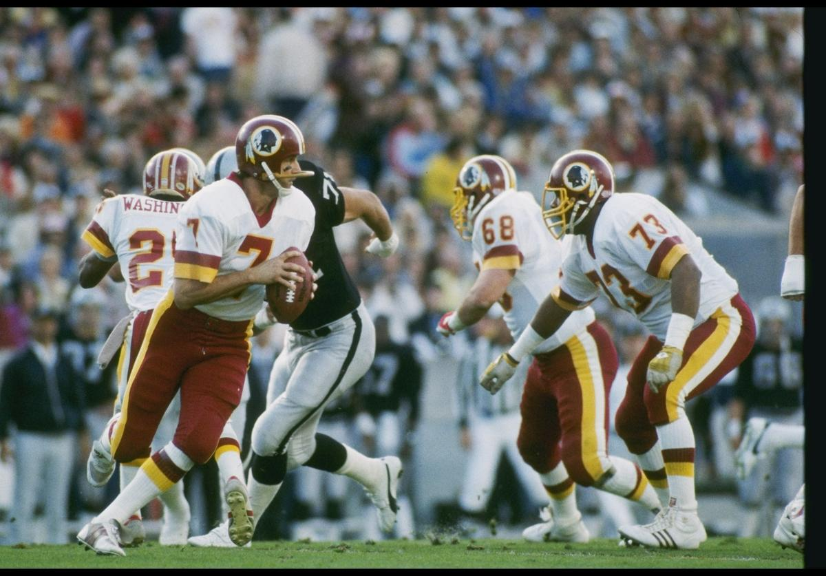 Quarterback Joe Theismann of the Washington Redskins looks to pass the ball during Super Bowl XVIII against the Los Angeles Raiders at Tampa Stadium in Tampa, Florida. The Raiders won the game, 38-9.