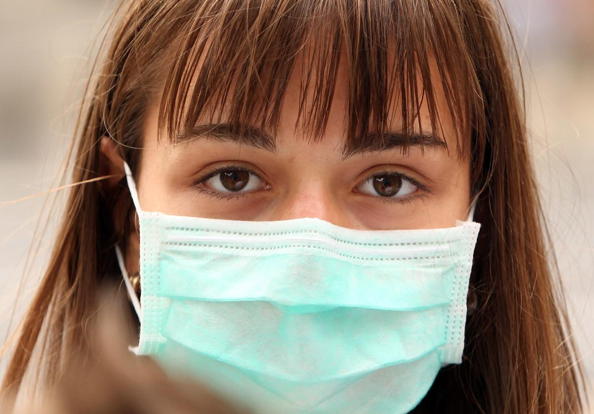 A woman wearing a surgical mask to prevent the transmission of airborne infection walks in Westminster on July 30, 2009 in London, England.