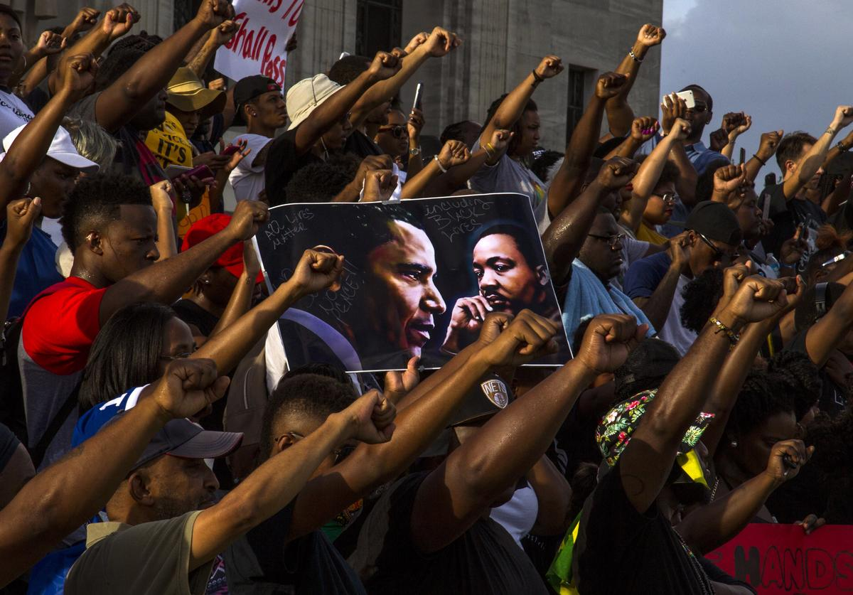 Demonstrators gather after marching at the Louisiana Capitol to protest the shooting of Alton Sterling on July 9, 2016 in Baton Rouge, Louisiana. Alton Sterling was shot by a police officer in front of the Triple S Food Mart in Baton Rouge on July 5th, leading the Department of Justice to open a civil rights investigation.