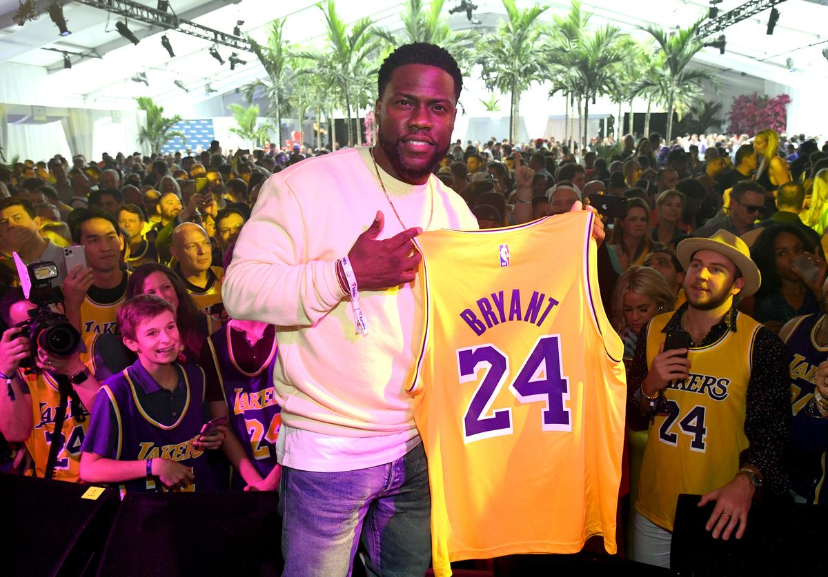 Kevin Hart poses onstage with a Kobe Bryant jersey during Michael Rubin's Fanatics Super Bowl Party