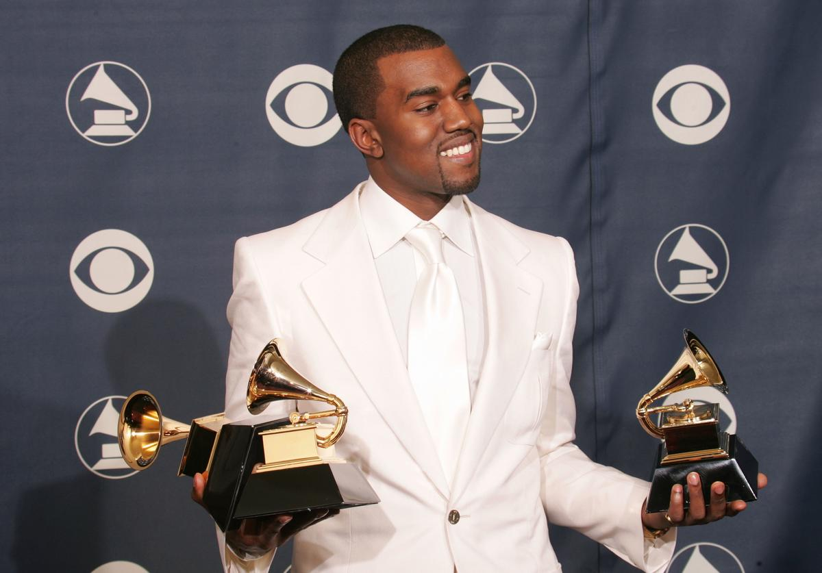 Kanye West poses with his Grammys at the Grammy press room