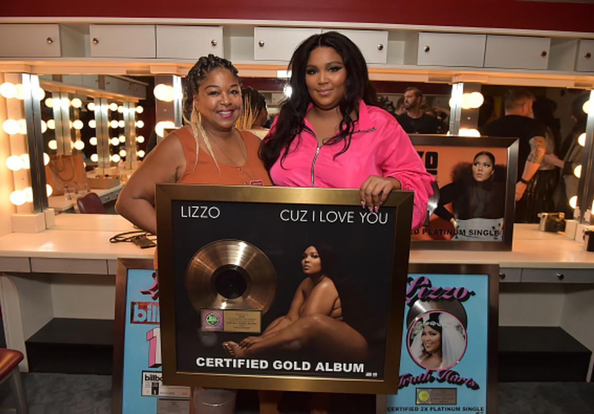 Lizzo accepts Gold plaque with mother.