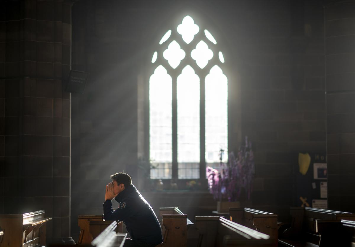 : A man prays in a church as shoppers make their last minute purchases on Christmas Eve on December 24, 2018 in Birmingham, England. Financial management consultancy Deloitte has predicted larger than normal discounts for boxing day sales as retailers aim to recuperate sales after a weak lead up to Chrismas.