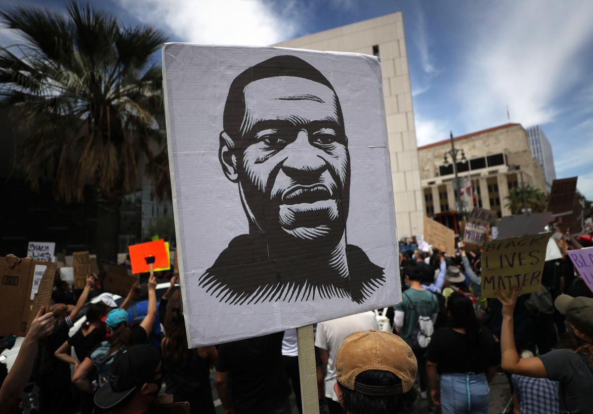 A protester holds a sign with an image of George Floyd during a peaceful demonstration over George Floyd's death outside LAPD headquarters on June 2, 2020