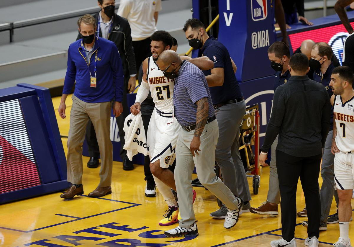 Jamal Murray #27 of the Denver Nuggets is helped off the court after an injury in their game against the Golden State Warriors at Chase Center on April 12, 2021 in San Francisco, California.
