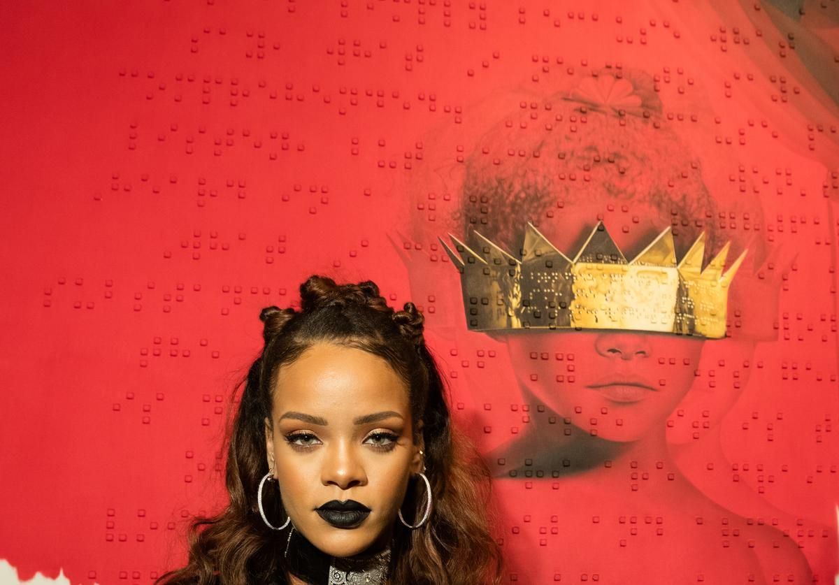 Rihanna standing in front of her 8th album cover