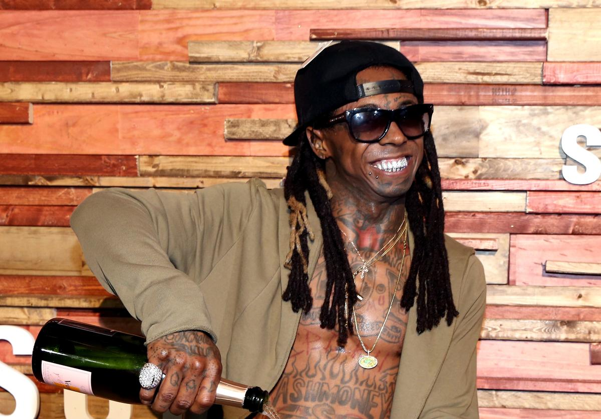 Rapper Lil Wayne pours champagne over his Samsung Galaxy S7 at Samsung Galaxy Life Fest at SXSW 2016 on March 12, 2016 in Austin, Texas