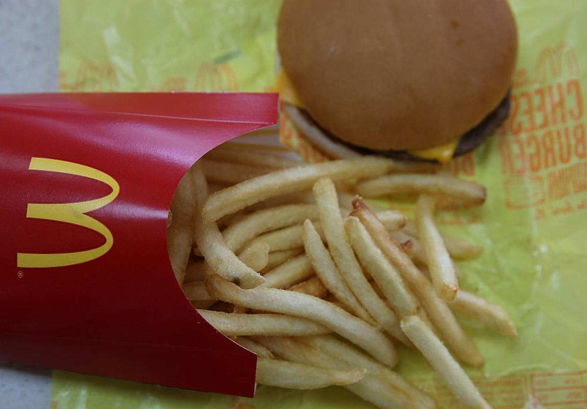 In this photo illustration, a McDonald's cheeseburger and fries are displayed on a table at a McDonald's restaurant on December 8, 2014 in Novato, California. McDonald's reported a worse than expected decline in November global same-restaurant sales.