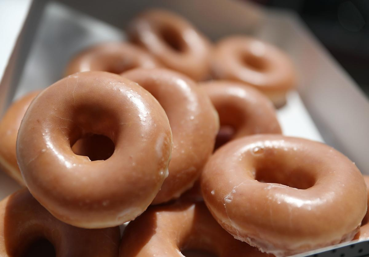 In this photo illustration, Krispy Kreme Donuts are seen on May 09, 2016 in Miami, Florida. JAB Holdings Company, announced it is acquiring Krispy Kreme Donuts in a deal valued at $1.35 billion.