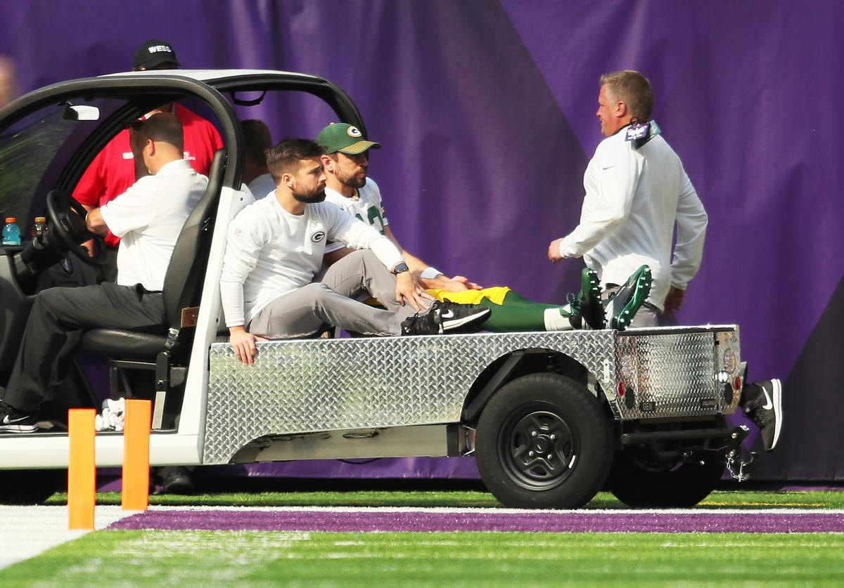 Aaron Rodgers #12 of the Green Bay Packers rides a cart into the locker room after being injured during the first quarter of the game against the Minnesota Vikings on October 15, 2017