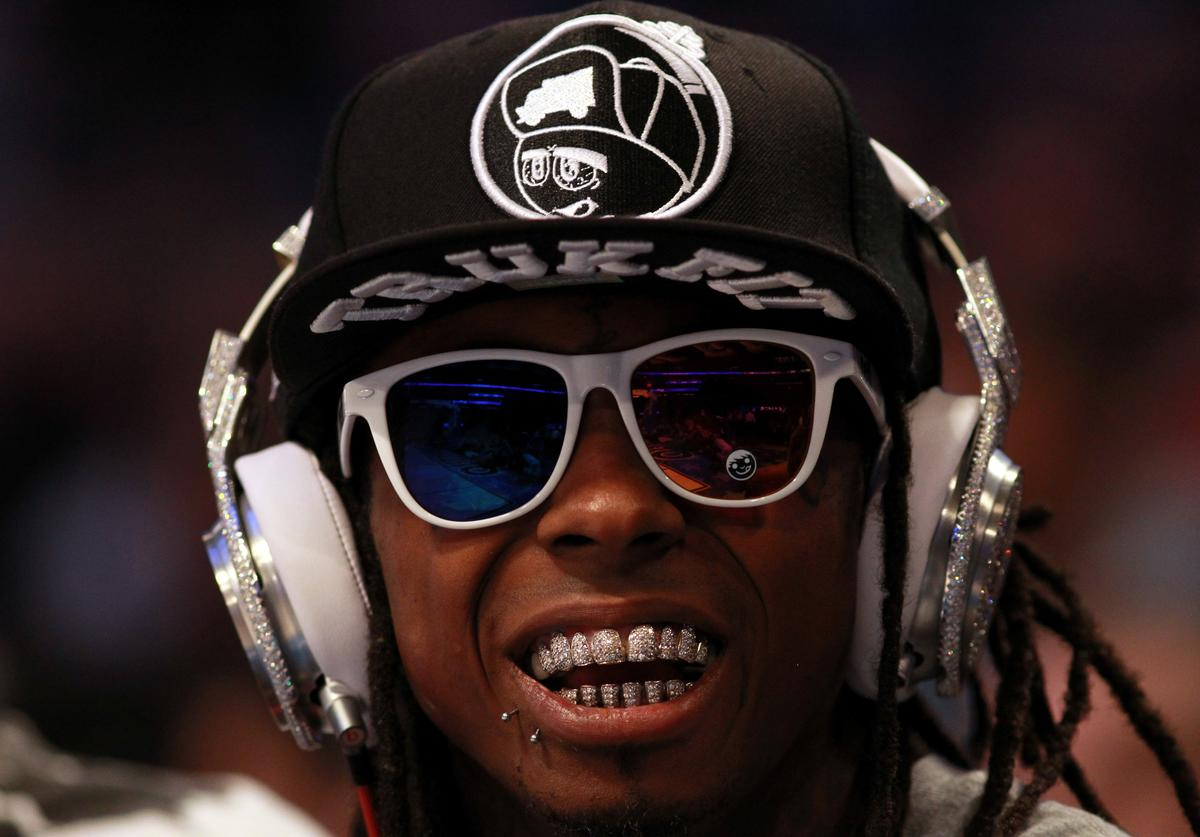 Hip-hop artists Lil' Wayne, wearing diamond studded beats headphones by Dr. Dre sits courtside during the 2012 NBA All-Star Game at the Amway Center on February 26, 2012 in Orlando, Florida