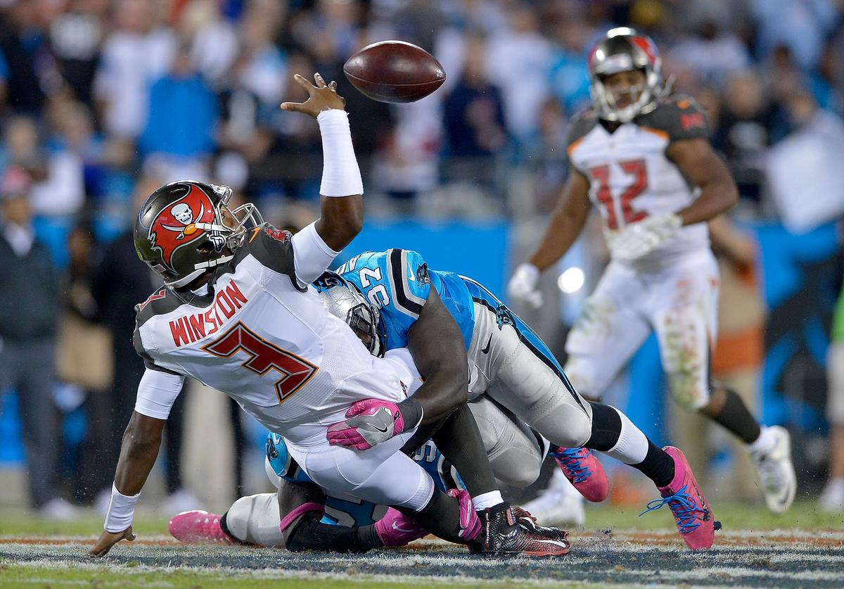 Mario Addison #97 of the Carolina Panthers forces a fumble as he hits Jameis Winston #3 of the Tampa Bay Buccaneers during the game at Bank of America Stadium on October 10, 2016 in Charlotte, North Carolina