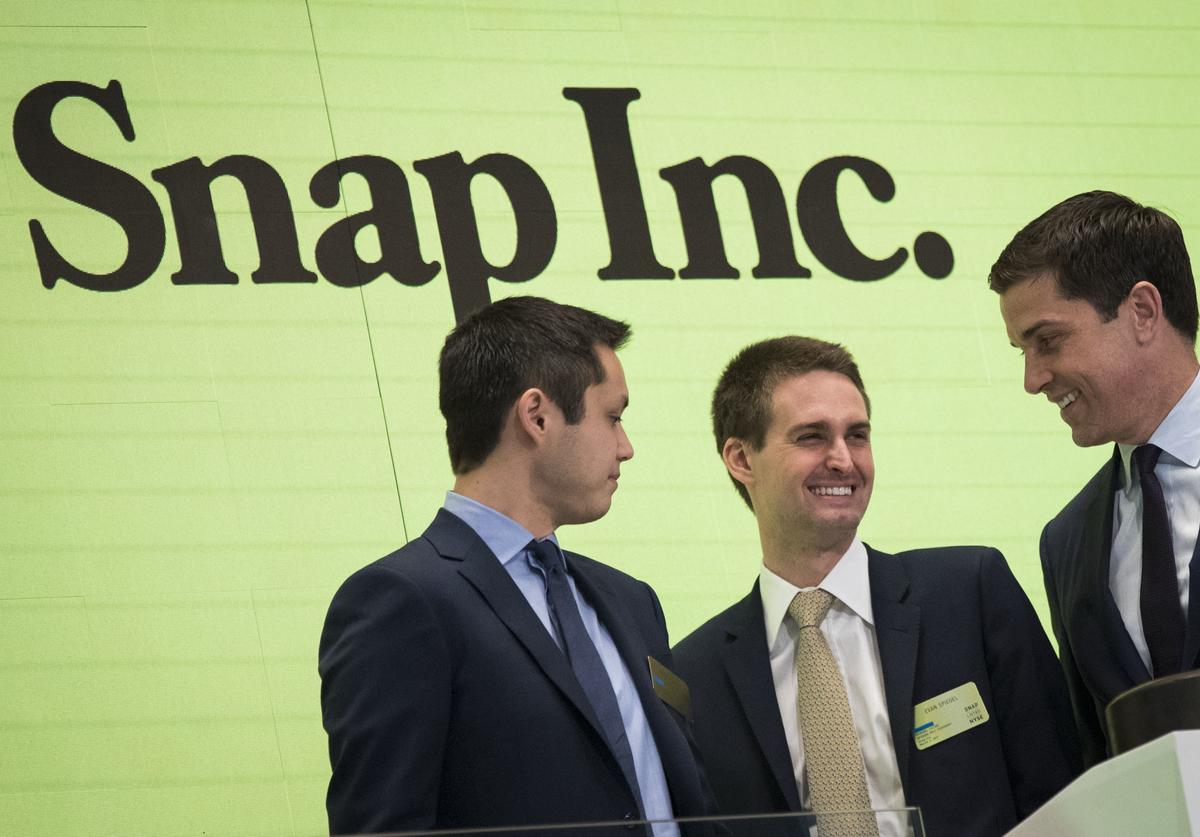 Snapchat co-founders Bobby Murphy, chief technology officer of Snap Inc., and Evan Spiegel, chief executive officer of Snap Inc., smile at each other after ringing the opening bell as Thomas Farley, president of the NYSE, looks on, March 2, 2017 in New York City. Snap Inc. priced its initial public offering at $17 a share on Wednesday and Snap shares will start trading on the New York Stock Exchange (NYSE) on Thursday