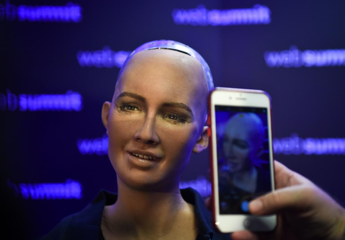 A woman takes pictures of Humanoid 'Sophia The Robot' of Hanson Robotics during a press conference at the 2017 Web Summit in Lisbon on November 7, 2017. Europe's largest tech event Web Summit is held at Parque das Nacoes in Lisbon from November 6 to November 9