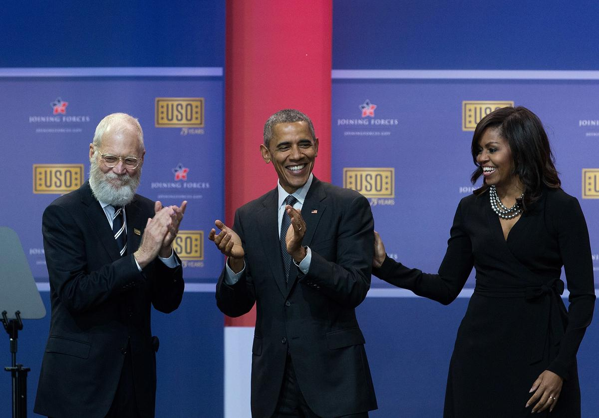 L to R, David Letterman, President Barack Obama and First Lady Michelle Obama laugh after signing 'Happy Birthday' to the USO in honor of their 75th anniversary, during a comedy show organized by United Services Organizations (USO) for members of the military and their families, at Andrews Air Force Base, May 5, 2016, in Joint Base Andrews, Maryland. The program is also being live streamed for active duty service members stationed at bases domestically and abroad