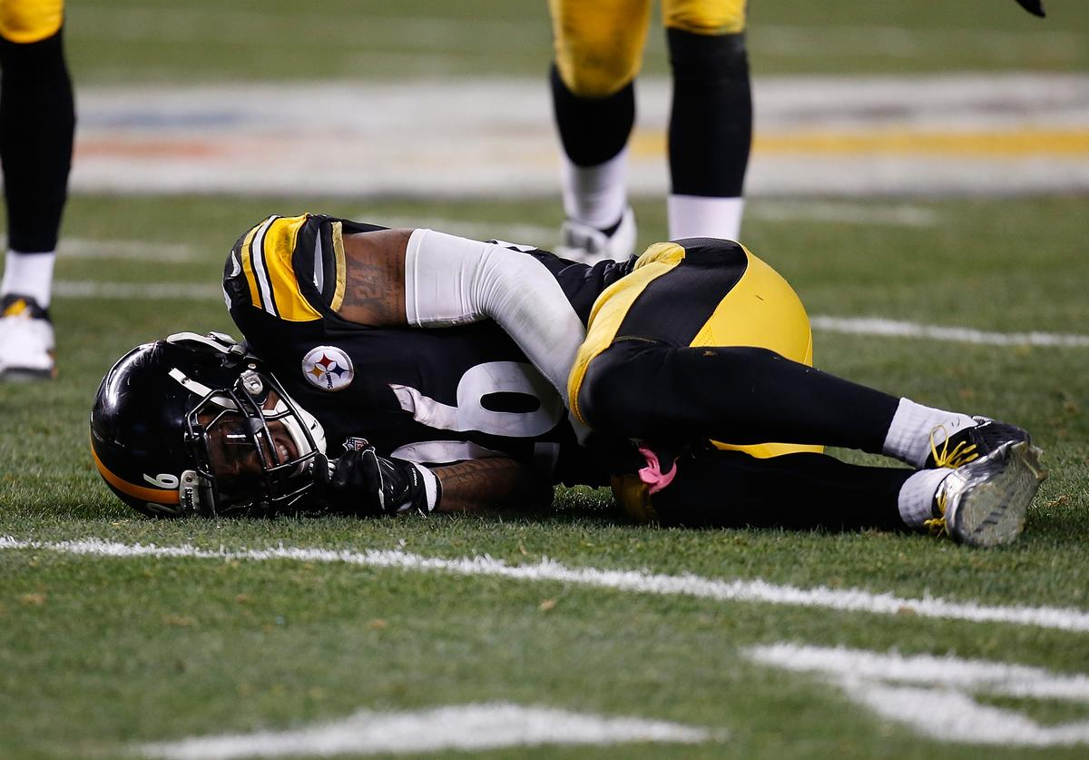 Le'Veon Bell #26 of the Pittsburgh Steelers is injured after being hit by Reggie Nelson #20 of the Cincinnati Bengals during the third quarter at Heinz Field on December 28, 2014 in Pittsburgh, Pennsylvania