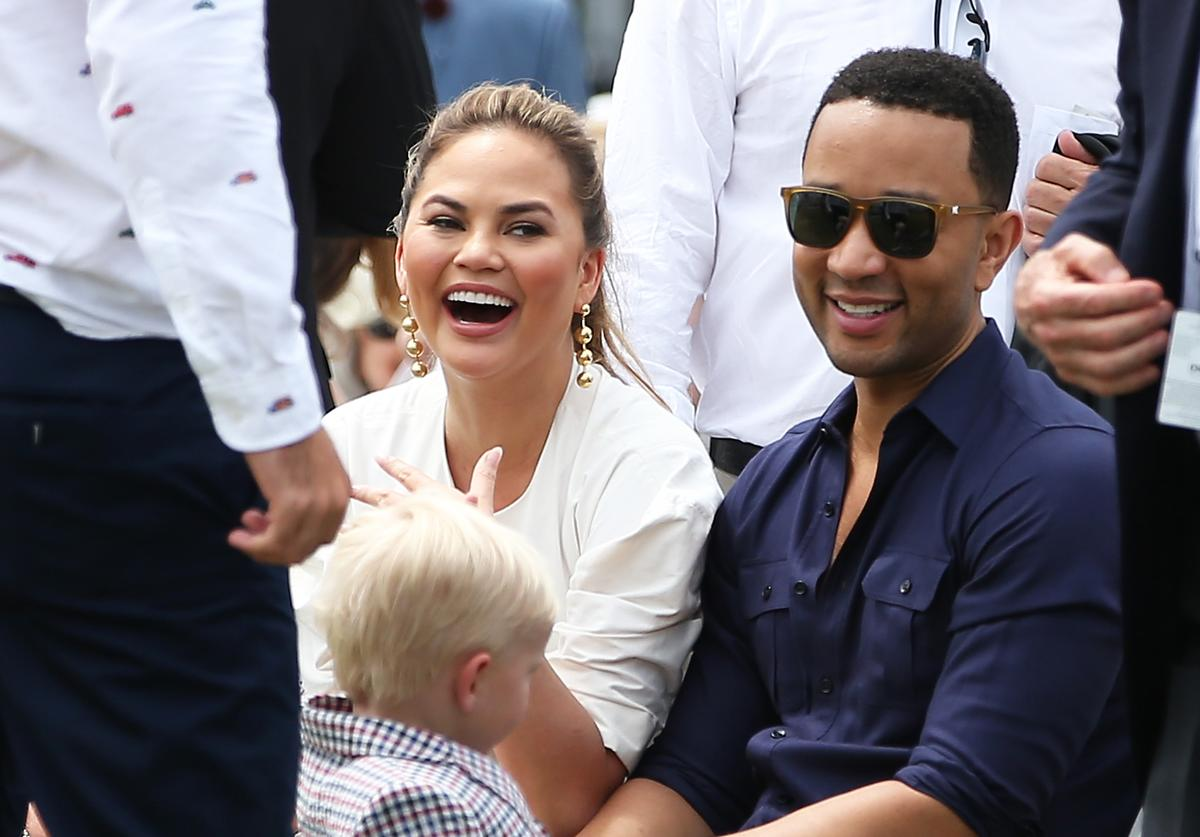 John Legend and Chrissy Teigen look on during the Tennis Hall of Fame induction ceremonies at the International Tennis Hall of Fame on July 22, 2017 in Newport, Rhode Island