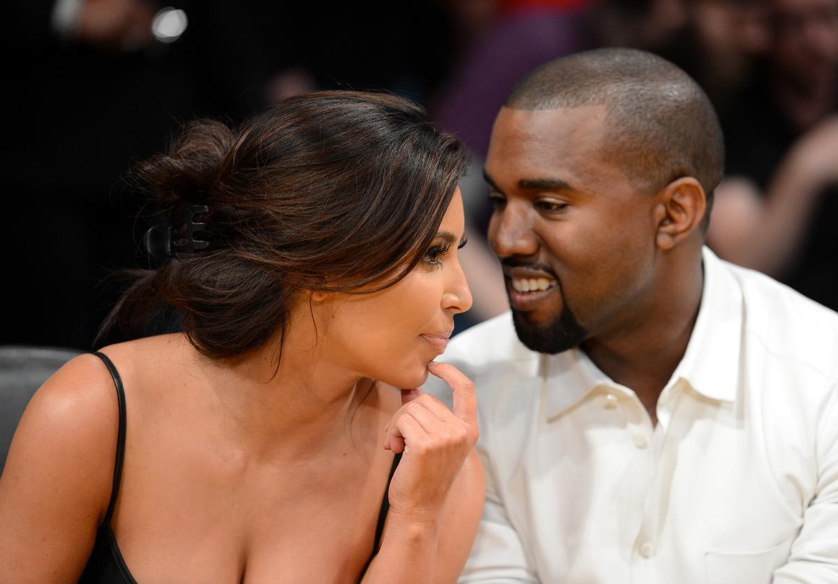 Kim Kardashian and rapper Kanye West talk from their courtside seats before the Los Angeles Lakers take on the Denver Nuggets in Game Seven of the Western Conference Quarterfinals in the 2012 NBA Playoffs on May 12, 2012 at Staples Center in Los Angeles, California.