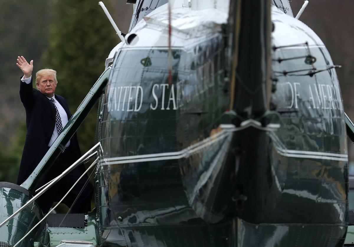 U.S. President Donald Trump waves to journalists as he boards Marine One on departure from Walter Reed National Military Medical Center following his annual physical examination January 12, 2018 in Bethesda, Maryland. Trump will next travel to Florida to spend the Dr. Martin Luther King Jr. Day holiday weekend at his Mar-a-Lago resort.
