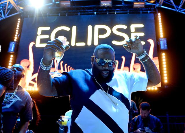 Rick Ross throwing his hands up at the club