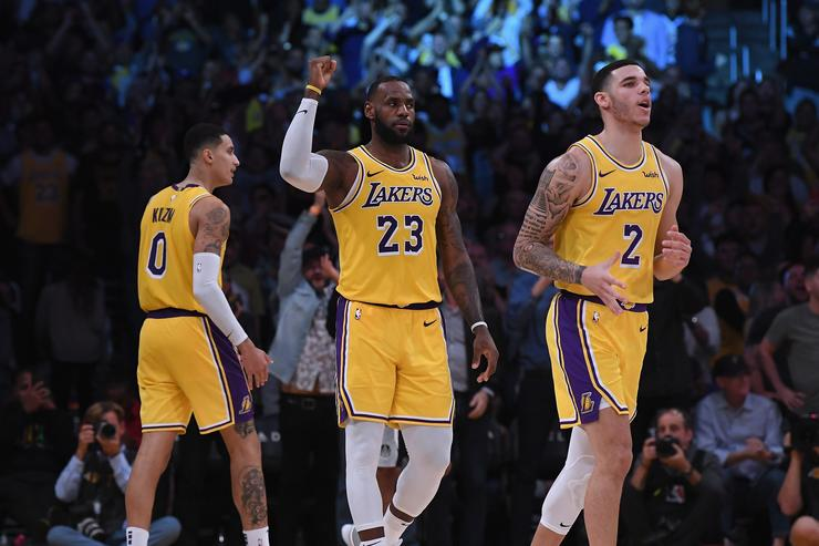 LeBron James #23 of the Los Angeles Lakers celebrates his basket in overtime between Lonzo Ball #2 and Kyle Kuzma #0 during a 143-142 loss to the San Antonio Spurs at Staples Center