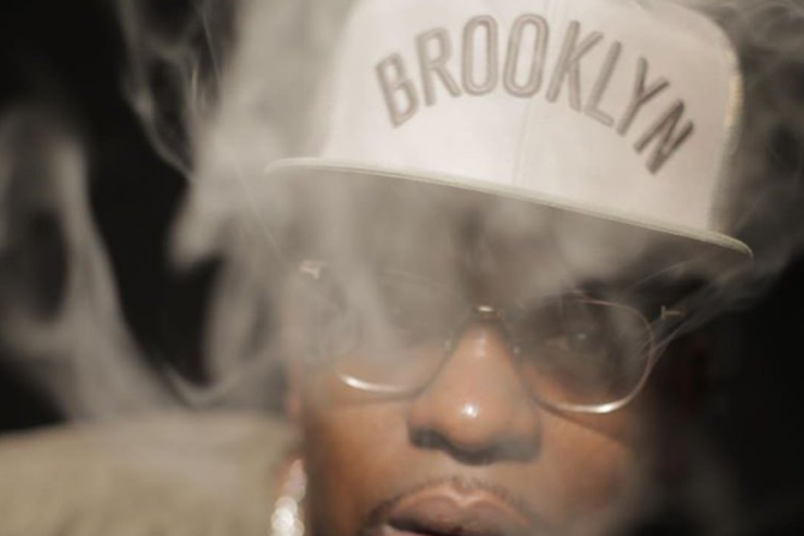 Uncle Murda holds a cigar amid some smoke.