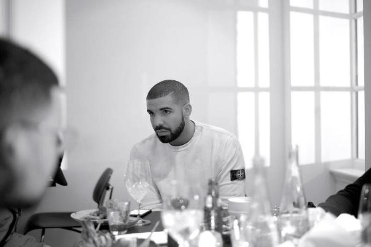 Drake sits at a table.