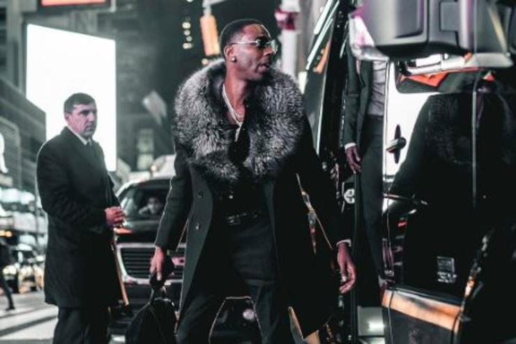 Young Dolph poses for a photo next to his SUV.