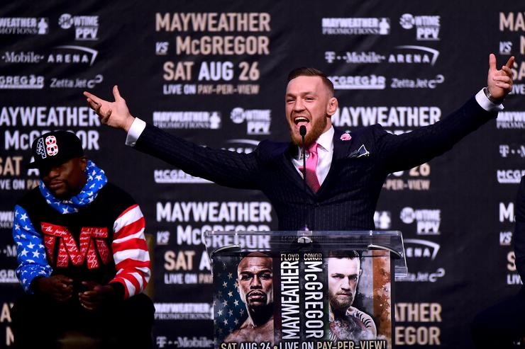 Conor McGregor speaks as Floyd Mayweather Jr. waits in the background during the Floyd Mayweather Jr. v Conor McGregor World Press Tour