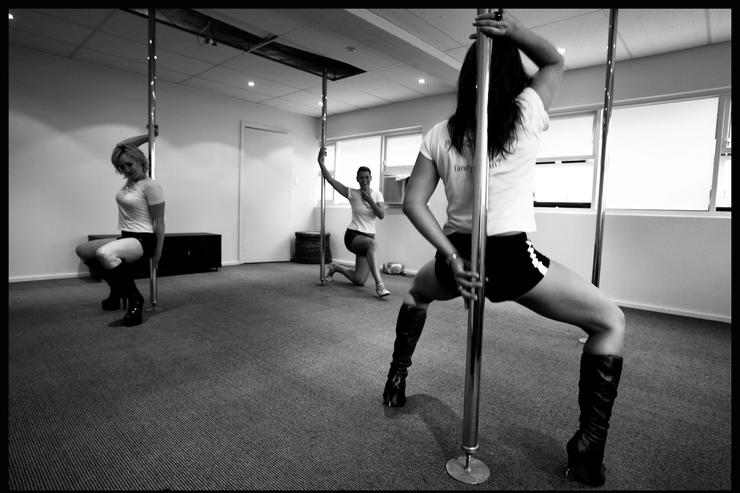 Poledancing students Danielle Grimmond (L) and Charlotte Priestley (C) practice moves on dance poles as Polestars Australia instructor Stephanie Kite (R) demonstrates during a poledancing lesson January 31, 2006 in Sydney, Australia.
