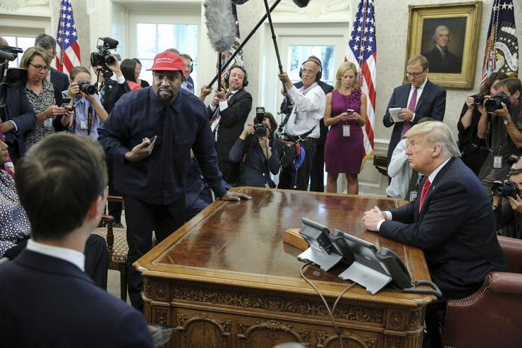 Rapper Kanye West, second left, stands up as he speaks during a meeting with U.S. President Donald Trump in the Oval office of the White House on October 11, 2018 in Washington, DC